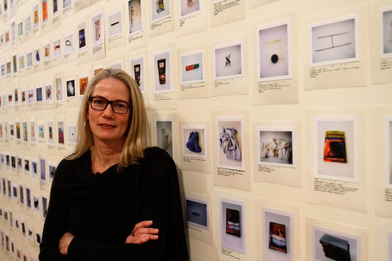 Artist Rachel Perry Welty with the 1,952 items she's photographed — and trashed. (Andrea Shea/WBUR)