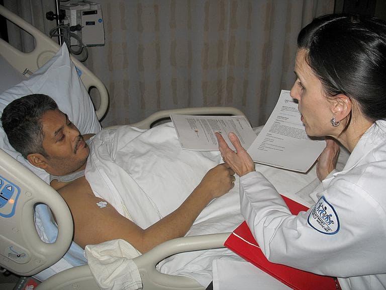 Kim Visconti, a special discharge nurse, talks to patient Edgardo LaSanta as he prepares to be discharged. (Martha Bebinger/WBUR)