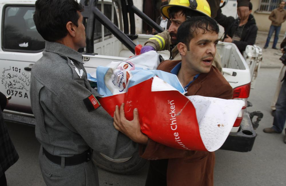 The body of a child wrapped in posters is brought out of a supermarket Jan. 28, 2011 in central Kabul, Afghanistan, after a bomb exploded inside, killing 14. (AP)