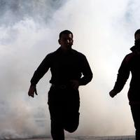 Bahraini demonstrators run from tear gas Monday, Feb. 14, 2011, as riot police disperse a protest in the village of Duraz, Bahrain, outside the capital of Manama. (AP)