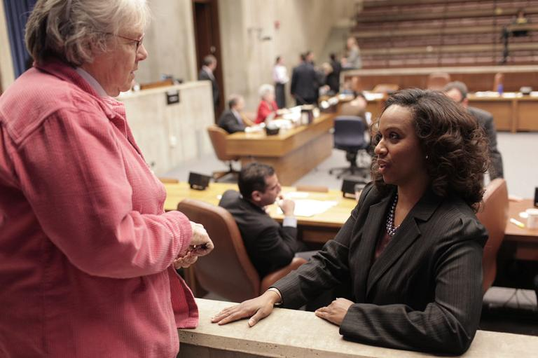 Boston City Councilor Ayanna Pressley, right, talks with Anne Schmalz, an observer from the League of Women Voters, at a recent council meeting. (Nick Dynan for WBUR)