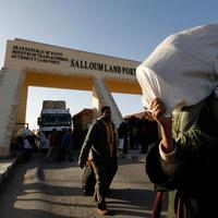 Egyptians who fled Libya carry their belongings through the Salloum land port gate at the Egyptian-Libyan border on Tuesday. (AP)