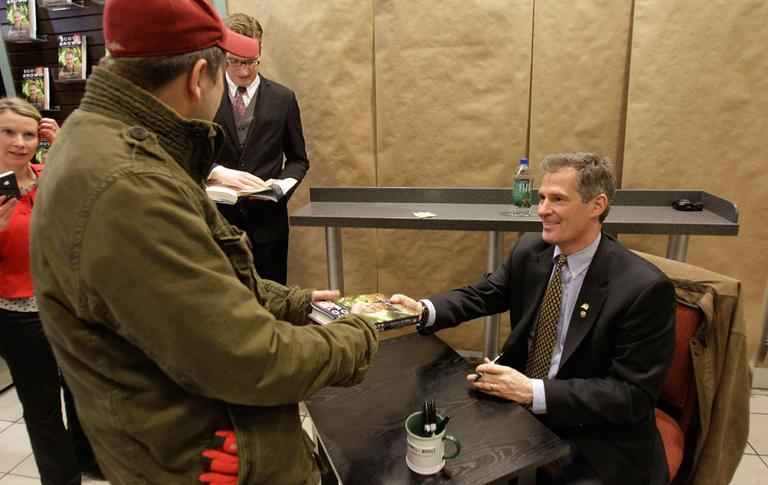 """Sen. Scott Brown hands his new book, """"Against All Odds,"""" back to a customer after signing the copy at Barnes & Noble in Boston on Tuesday. (AP)"""