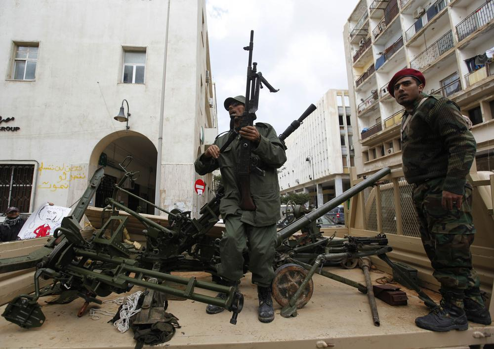 Gunmen prepared to fight against Libyan leader Moammar Gadhafi stand on a small military truck with weapons taken from a Libyan military base, in Benghazi, Libya. (AP)