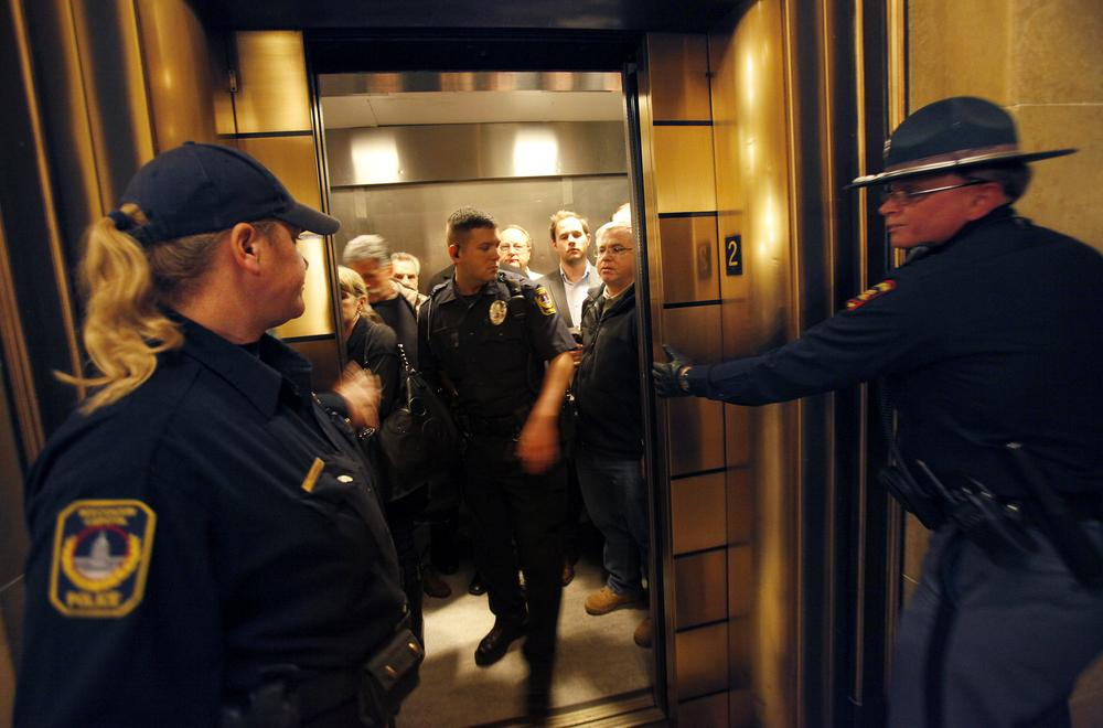 Escorted by law enforcement officers, Assembly Republicans exit the state Capitol after cutting off debate and rapidly voting to pass a controversial budget repair bill in the state Assembly in Madison, Wis. (AP)