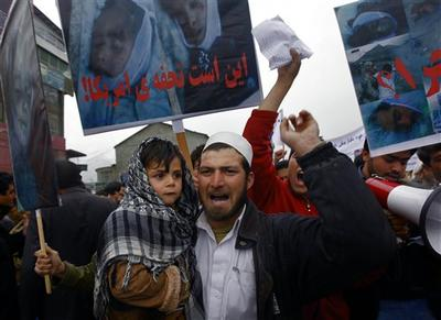 "An Afghan supporter of left wing political party holds his son as he shouts anti US slogans during a protest in Kabul, Afghanistan. Poster reads in Arabic ""Gift of America."" (AP)"
