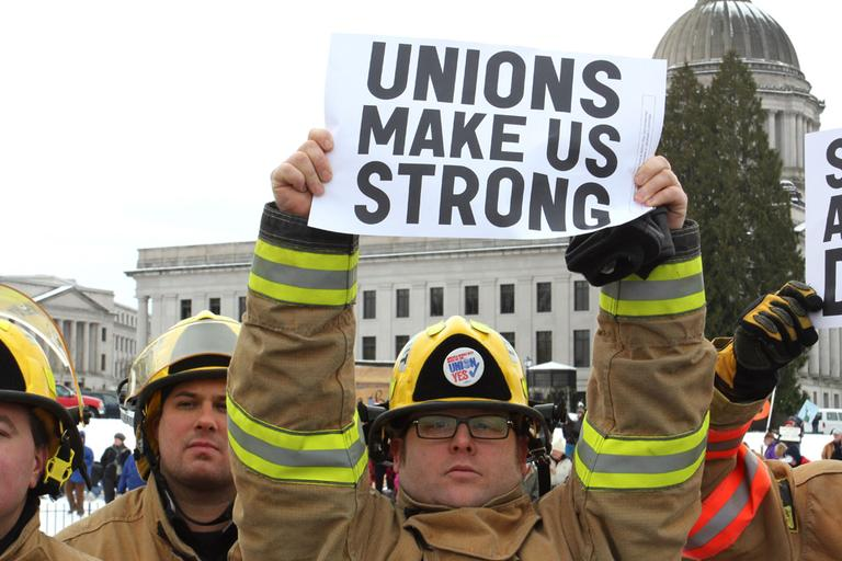 Firefigher Brian Ritter of Ocean Shores, Wash., holds a pro-union sign during a rally supporting Wisconsin public sector unions on the Capitol campus in Olympia, Wash. (AP)