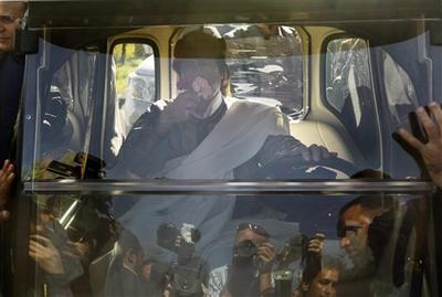Libyan Leader Moammar Gadhafi smells flowers given to him by a supporter as he drives away in an electric golf cart after speaking in Tripoli, Libya, Wednesday, March 2, 2011. (AP)