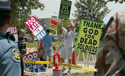 Supporters of the Rev. Fred Phelps, of the Topeka, Kan.-based Westboro Baptist Church, demonstrate outside the funeral service for Marine Lance Cpl. Rex Arthur Page, Sunday, July 9, 2006, in Kirksville, Mo. (AP)