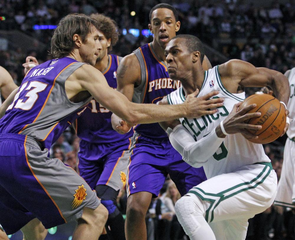 Boston Celtics point guard Rajon Rondo (9) makes a move against the defense of Phoenix Suns point guard Steve Nash (13) and center Channing Frye, middle, during the first quarter of the game in Boston on Wednesday. (AP)