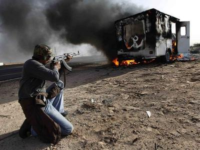 A Libyan rebel took aim at a burning vehicle used by pro-Moammar Gadhafi fighters in celebration of the rebel victory in Wednesday's battle for Brega. (AP)