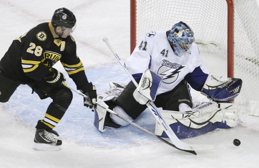 Boston Bruins left wing Mark Recchi, left, tries to get his stick on the rebound as Tampa Bay Lightning goalie Mike Smith, right, makes the save during the first period of an NHL hockey game in Boston on Thursday. (AP)