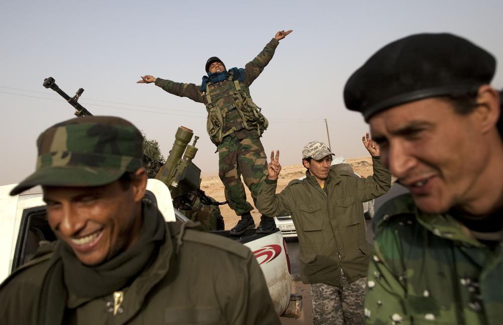 Libyan rebels who are part of the forces against leader Moammar Gadhafi celebrate their victory in fighting against troops loyal to Gadhafi in the oil town of Ras Lanuf, eastern Libya, on Saturday. (AP)