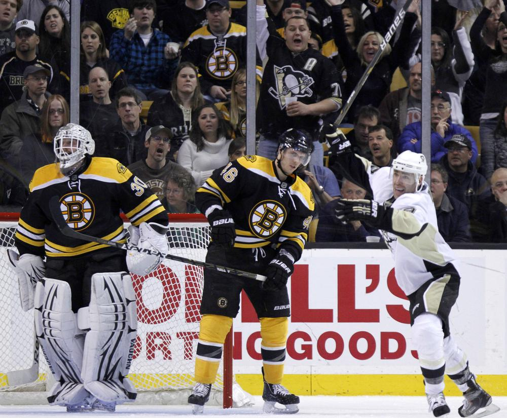 Penguins' Pascal Dupuis, right, celebrates a goal by teammate Dustin Jeffrey as  Bruins' Tim Thomas, left, and David Krejci, center, look on in the second period on Saturday in Boston. (AP)