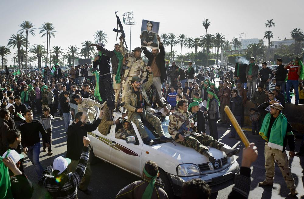 Pro-Gadhafi soldiers and supporters gather in Green Square in Tripoli, Libya Sunday. Thousands of Moammar Gadhafi's supporters poured into the streets of Tripoli on Sunday morning, waving flags and firing their guns in the air in the Libyan leader's main stronghold, claiming overnight military successes. (AP)