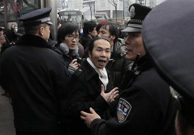 A man, center, confronts with police officers in front of a cinema that was a planned protest site in Shanghai, China. (AP)