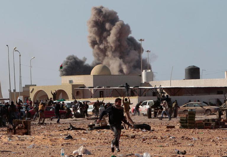 An anti-Gadhafi rebel runs away as smoke rises following an airstrike by Libyan warplanes in Ras Lanouf, eastern Libya, on Monday. (AP)