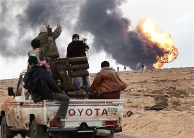 Anti-Gadhafi rebels ride on a truck with a multiple rocket launcher, as flames rises from a fuel storage facility that was attacked during  fighting with pro-fighters, in Sedra, eastern Libya. (AP)