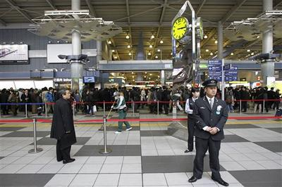 A worker cleans the floor at Tokyo's Shinagawa station where an object fell after a magnitude 8.9 earthquake slammed Japan's eastern coast. (AP)
