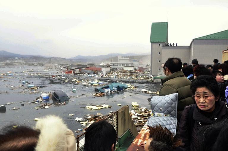 People watch the aftermath of tsunami tidal waves covering a port at Kesennuma in northern Japan, Friday. (AP/Keichi Nakane, The Yomiuri Shimbun)