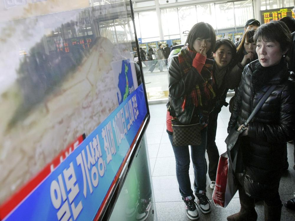 Japanese tourists watch a TV news program about a strong earthquake hitting their country at Seoul Railway Station in Seoul, South Korea on Friday. (AP)