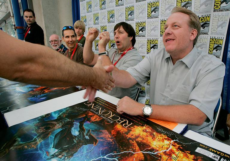 """At right, former Red Sox pitcher Curt Schilling shakes hands with a fan at Comic-Con in July 2010 in San Diego. Schilling's 38 Studios will demo """"Kingdoms of Amalur: Reckoning"""" at this weekend's PAX East in Boston. (AP/Electronic Arts)"""