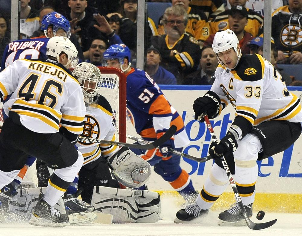 Bruins' Zdeno Chara (33) drives the puck away from New York Islanders' Michael Grabner (40) of Austria and Frans Nielsen (51) of Demark as Bruins'  David Krejci (46) of the Czech Republic and goalie Tim Thomas (30) defend during the third period Friday, March 11, 2011, in Uniondale, N.Y. (AP Photo/Kathy Kmonicek)