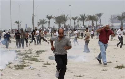 Anti-government protesters react to tear gas fired by riot police along a main highway in Manama, Bahrain. (AP)
