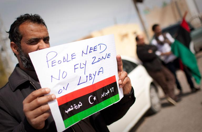 A Libyan man holds up a sign asking for a no-fly zone over Libya near the border town of Musa'id, Libya, on Sunday. (AP)