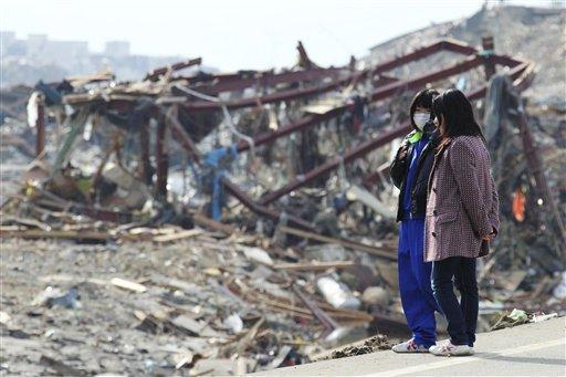 People look at a devastated area of Minamisanriku, northern Japan, Monday, three days after a powerful earthquake-triggered tsunami hit the country's east coast. (AP)