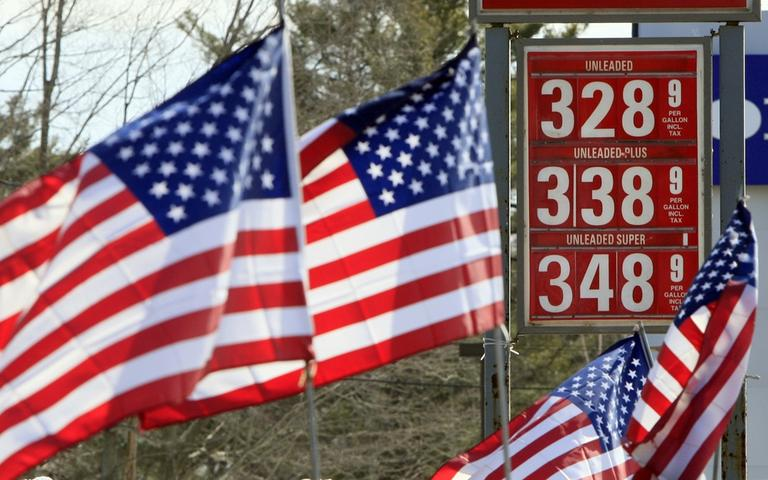 American flags blow in the wind outside a Gibbs gas station in Topsham, Maine, where a sign showed the price of gasoline in February. (AP)