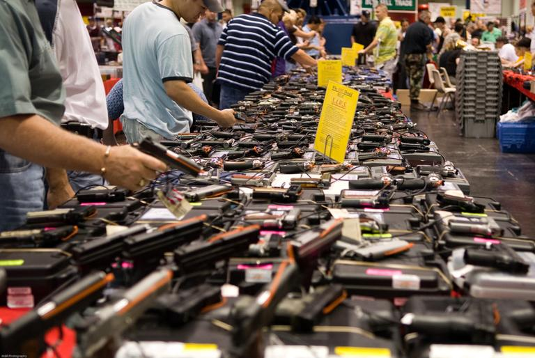 Attendees at a gun show in Houston sort through potential purchases. (M Glasgow/Flickr)