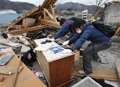Richi Shida, right, and younger brother Kento try to open their chest of drawers at Ofunato, Iwate Prefecture, northern Japan. (AP)