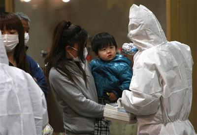 A child is screened for radiation exposure at a testing center in Koriyama city, Fukushima Prefecture, Japan. (AP)