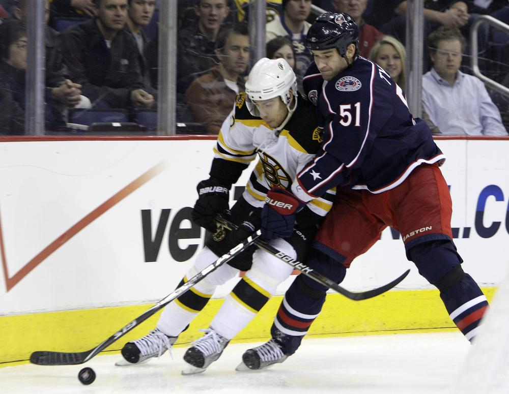 Columbus Blue Jackets' Fedor Tyutin, right, of Russia, and Boston Bruins' Chris Kelly chase a loose puck during the first period of the game on Tuesday in Columbus, Ohio. (AP)