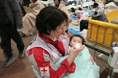 A baby survivor is fed milk by a member of Japanese RC's National Disaster Response Team at the Ishinomaki Red Cross Hospital in Ishinomaki in Miyagi Prefecture. (AP/Japanese Red Cross)