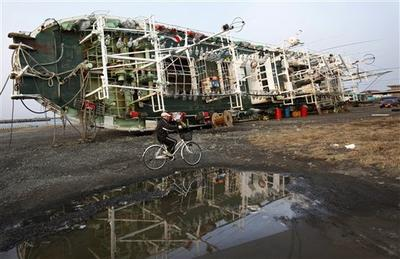 A man cycles by a ship at Hachinohe, Aomori prefecture, northern Japan.  Hachinohe lies north of Shichigahama, a sister city of Plymouth, Mass. (AP/Shizuo Kambayashi)