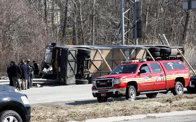 At least 13 people died when a bus, returning to New York from a casino in Connecticut, flipped onto its side and was sliced in half by the support pole for a large sign. (AP)