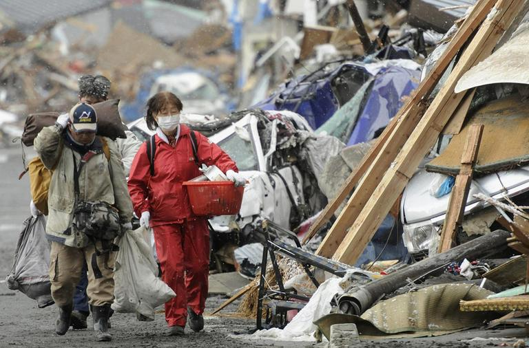 Survivors of Friday's earthquake and tsunami walk with their belongings by the rubble in Kamaishi in northern Japan. (AP)