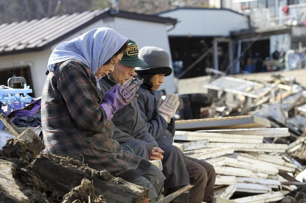 Survivors pray for victims at the devastated city of Miyako, northeastern Japan. (AP/Yomiuri Shimbun, Naoya Masuda)