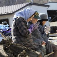 Survivors pray for victims at the devastated city of Miyako, northeastern Japan. (AP/Yomiuri Shimbun, Naoya Masuda)