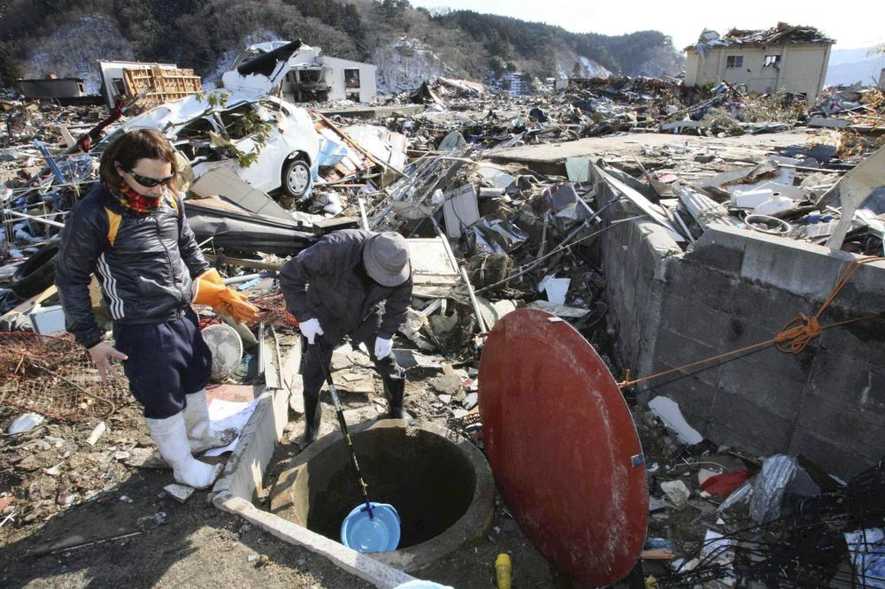 Survivors use a plastic bucket to get water from a well at the devastated town of Yamada, northeastern Japan. (AP/Yomiuri Shimbun, Takashi Ozaki)