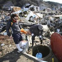 Survivors use a plastic bucket to get water from a well at the devastated town of Yamada, northeastern Japan. (AP)