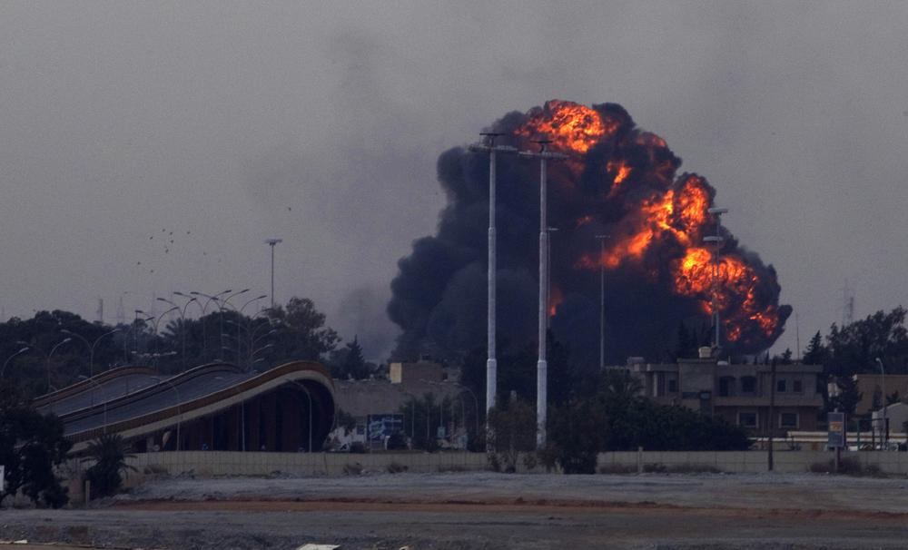 A huge explosion is seen over the outskirts of Benghazi after a plane of Gadafi's forces was shot down over eastern Libya Saturday. (AP)