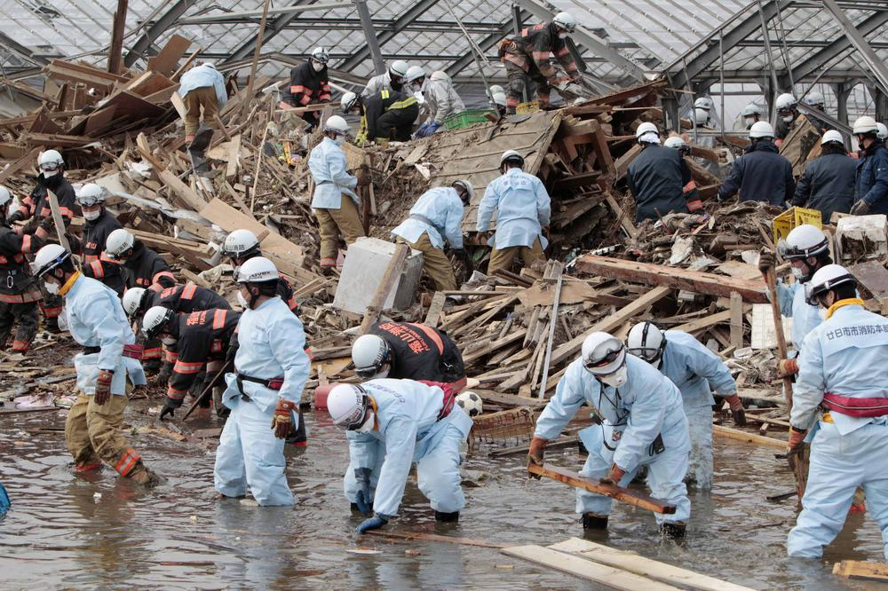 Rescue workers sift through the remains of a property in the suburb of Natori, Sendai, Miyagi Prefecture, Japan, Sunday, March 20, 2011 after the March 11 earthquake and tsunami devastated the area.  (AP)