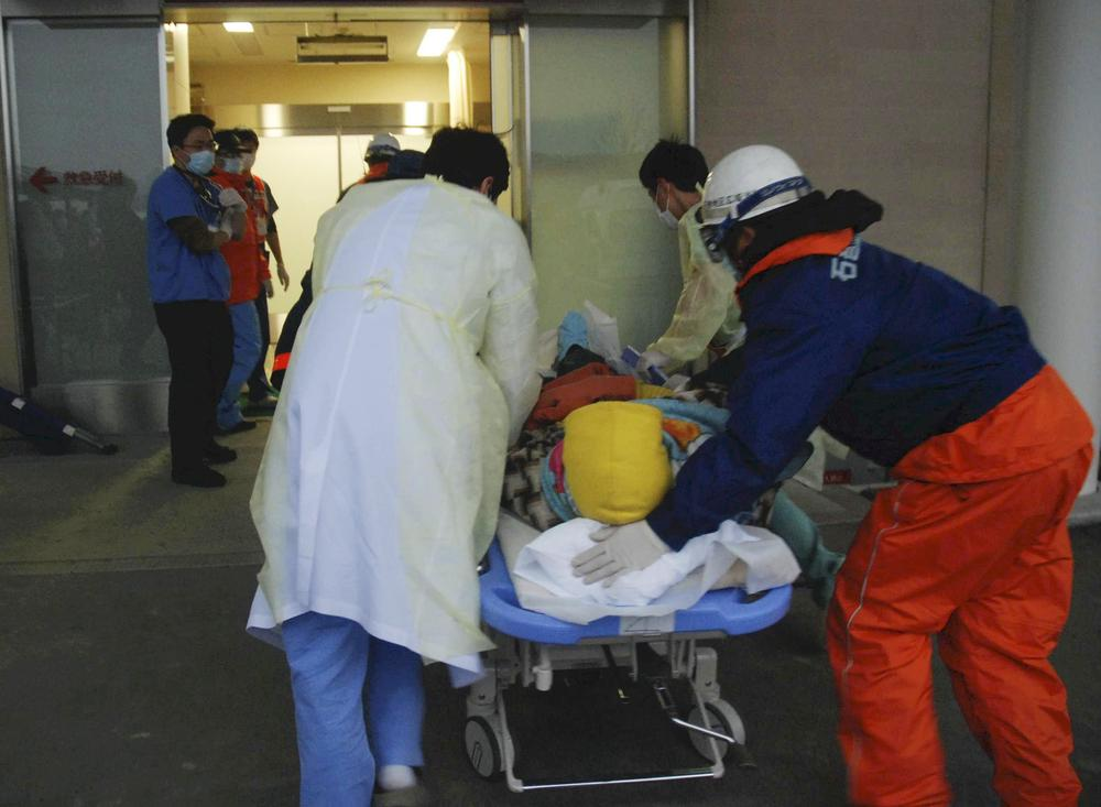 A woman on a stretcher gets carried into the Ishinomaki Red Cross Hospital in Ishinomaki, northern Japan, Sunday, after the March 11 earthquake and tsunami.  (AP Photo/The Yomiuri Shimbun, Masanori Yamashita)
