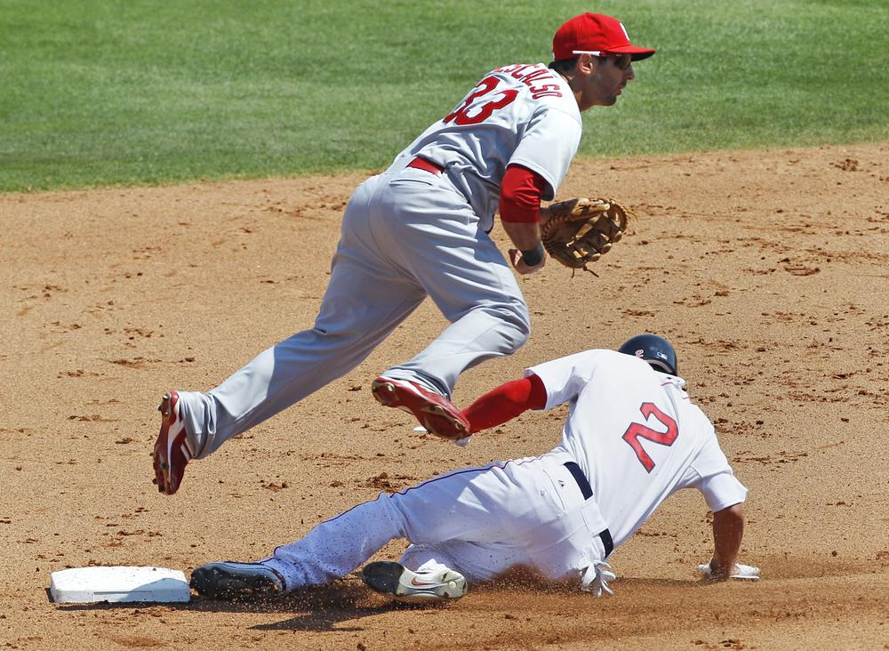 St. Louis Cardinals second baseman Daniel Descalso, top, leaps over Boston Red Sox's Jacoby Ellsbury (2) on a double play hit into by Dustin Pedroia in the third inning of a spring training baseball game in Fort Myers, Fla., Sunday. (AP)