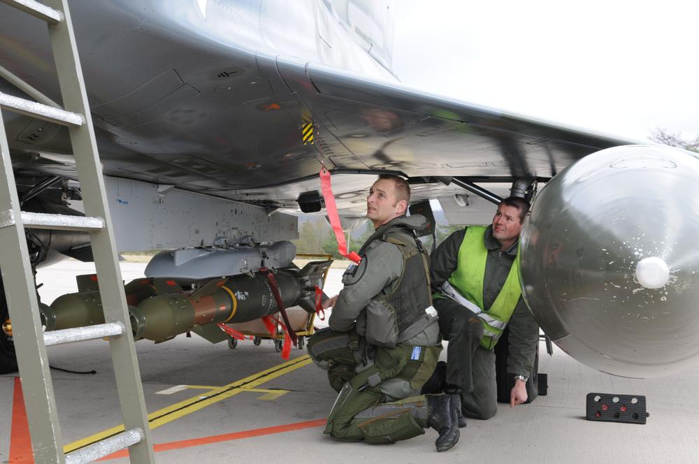 Soldiers fix a GBU.12 bomb on a French Mirage 2000 jet fighter at the military base of Nancy, eastern France. The Mirages 2000 are operating over Libya. (AP/SIRPA AIR)