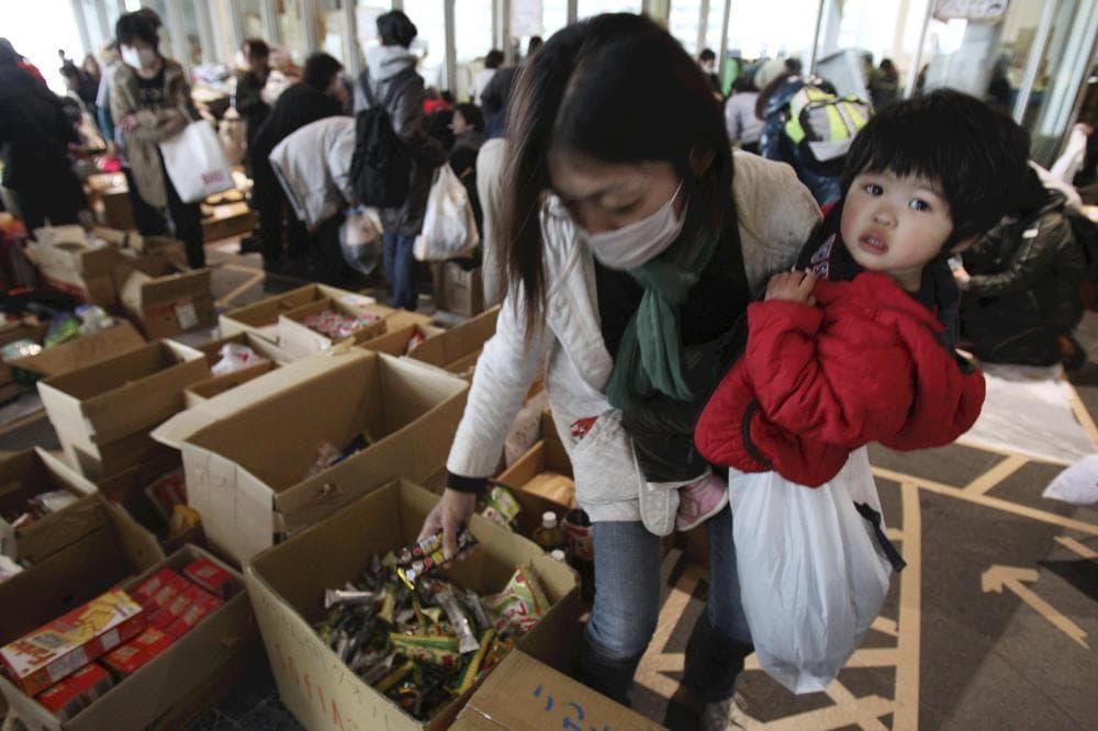 An evacuee mother receives emergency food aid at the evacuation center set up at Saitama Super Arena in Saitama, Japan. (AP/The Yomiuri Shimbun, Jun Yasukawa)