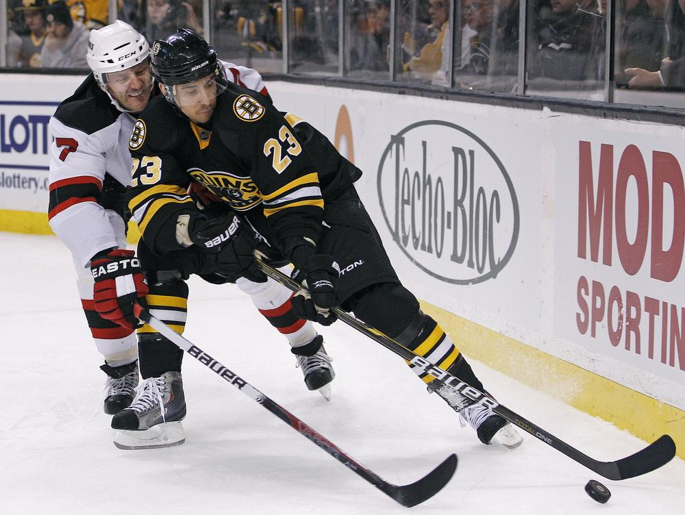 New Jersey Devils defenseman Henrik Tallinder (7) vies for the puck with Boston Bruins center Chris Kelly (23) during the second period of the game in Boston on Tuesday. (AP)